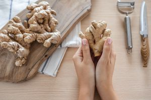 two hands hold large unpeeled ginger root next to metal peeler and knife and cutting board