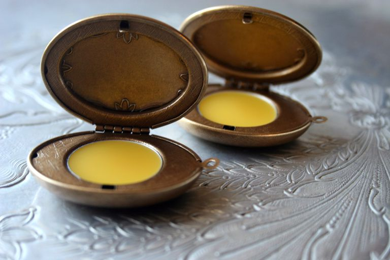 Solid perfume in antique looking bronze cases.
