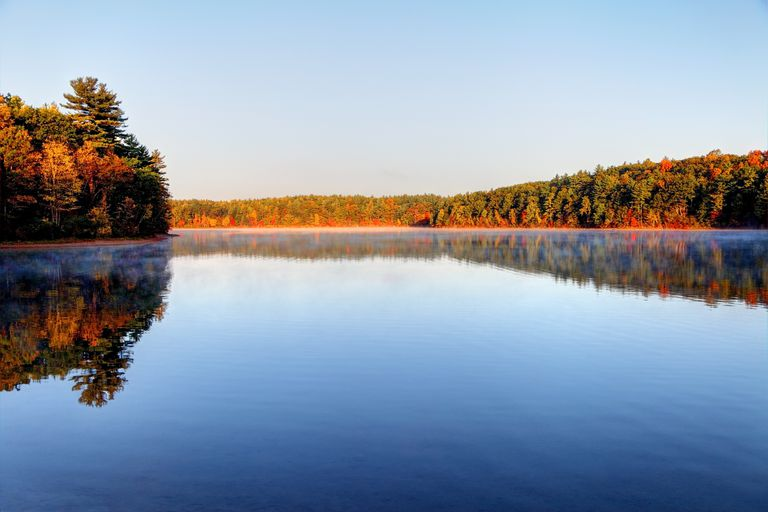 Autumn on Walden Pond with perfectly flat, blue water surrounded by colorful trees with a light blue sky above