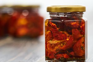 Small jar of sun-dried tomatoes on a wooden table
