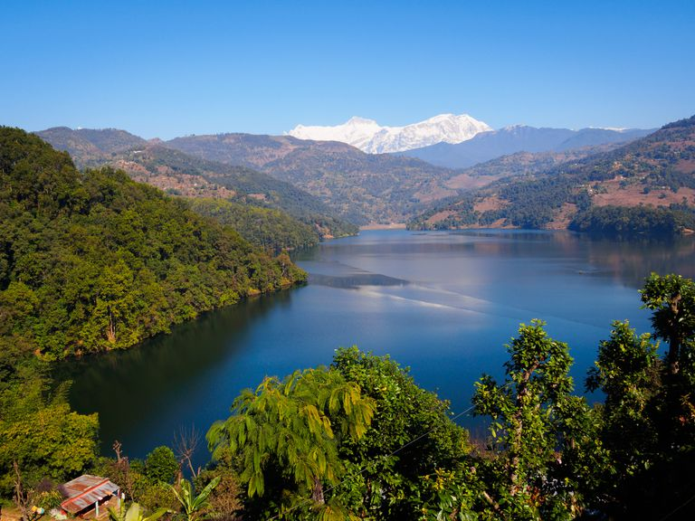 lake surrounded by forested hills with snowy mountain in background