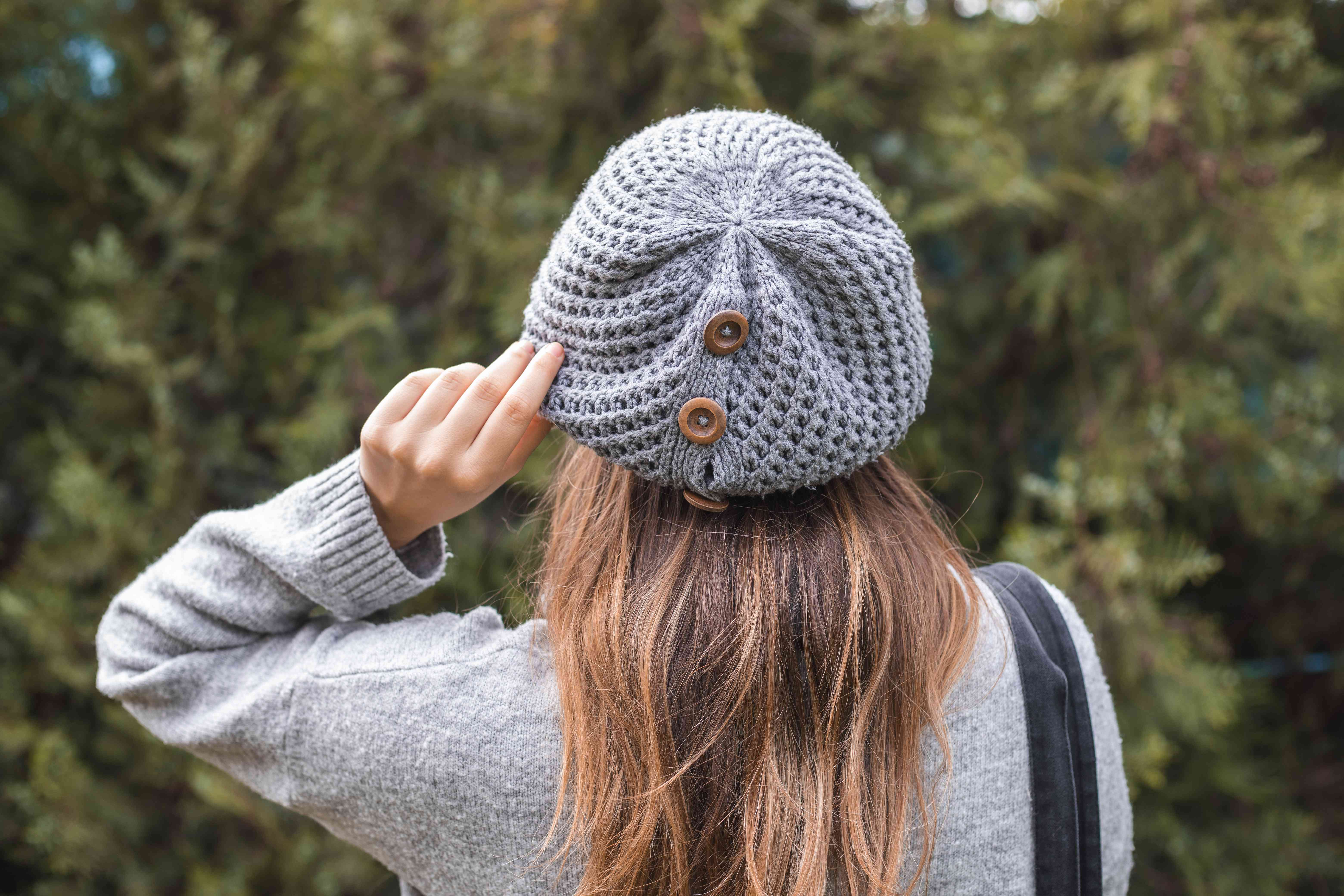 slouchy chunky sweater beanie with brown buttons on model with long hair