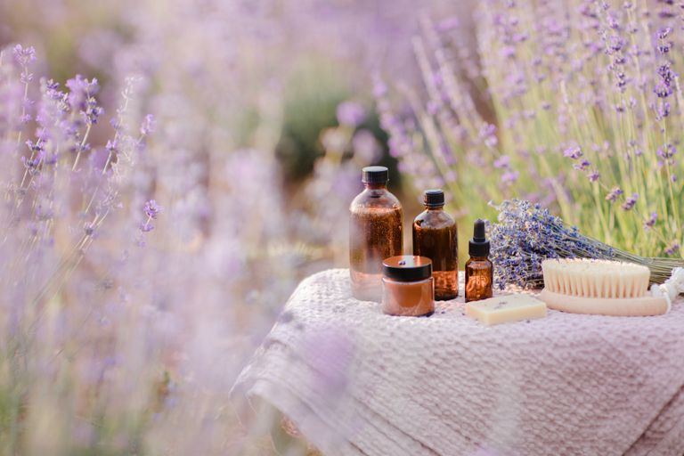Organic cosmetics bottles, essential oil and soap in lavender field in the summer. Aromatherapy. Skincare concept.