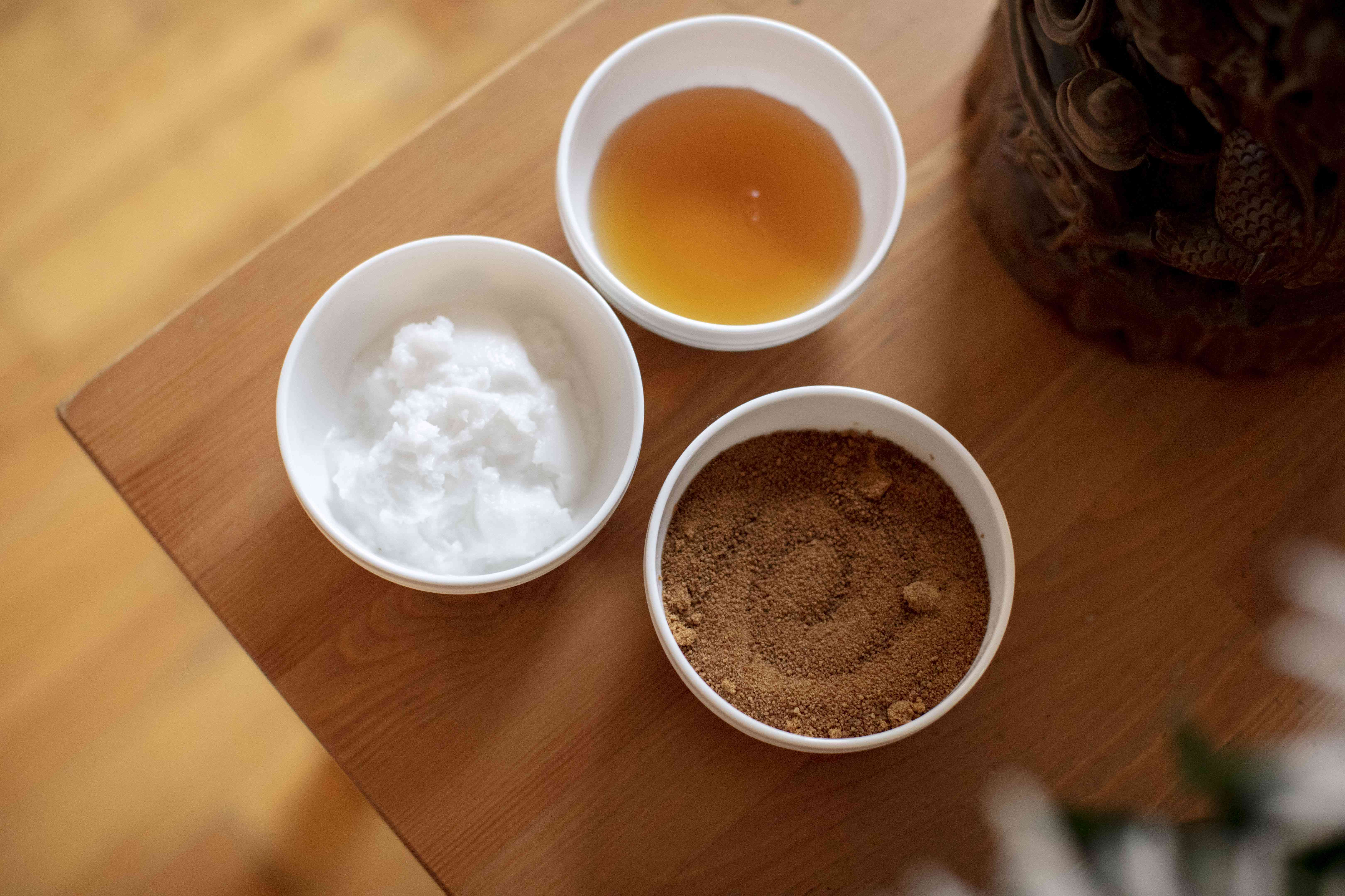 coconut sugar, coconut oil, and honey in white ceramic bowls on wooden table for diy lip scrub