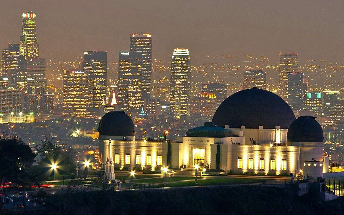 Griffith Observatory at night with the Los Angeles skyline behind it