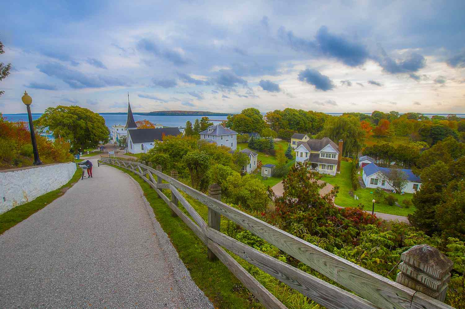 A person walks a bicycle up a path on Mackinac Island in Michigan