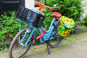 A blue bike with a milk crate and bungee cord basket.
