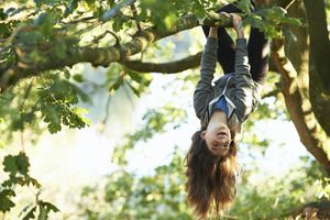 girl hangs from tree
