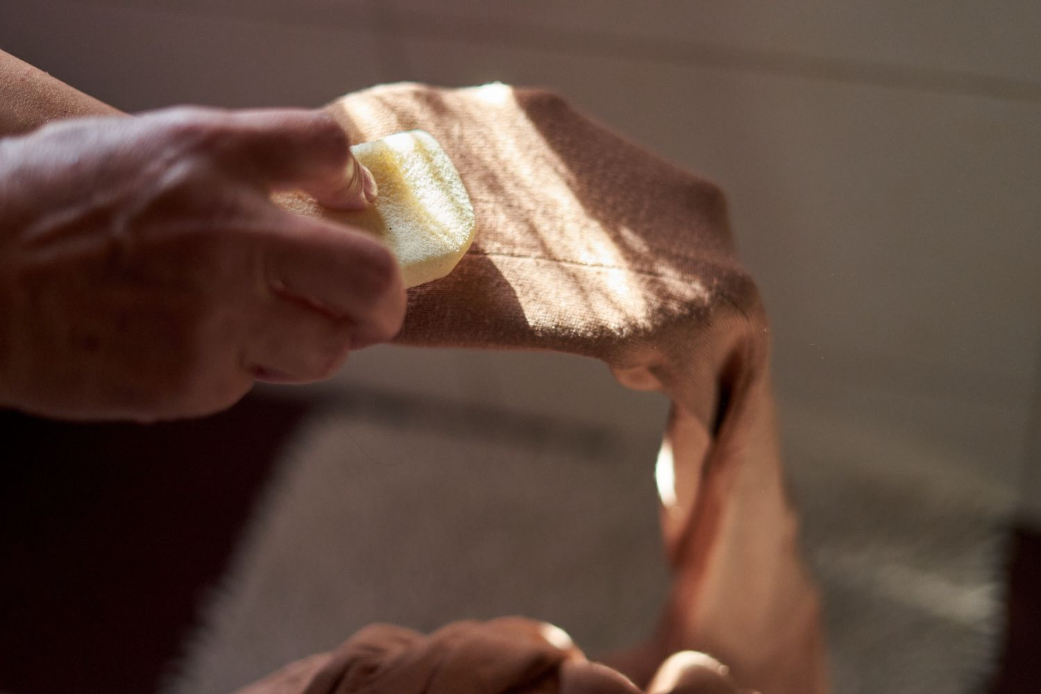 hands gently rub cream-colored pumice stone in arm of brown sweater to remove pills