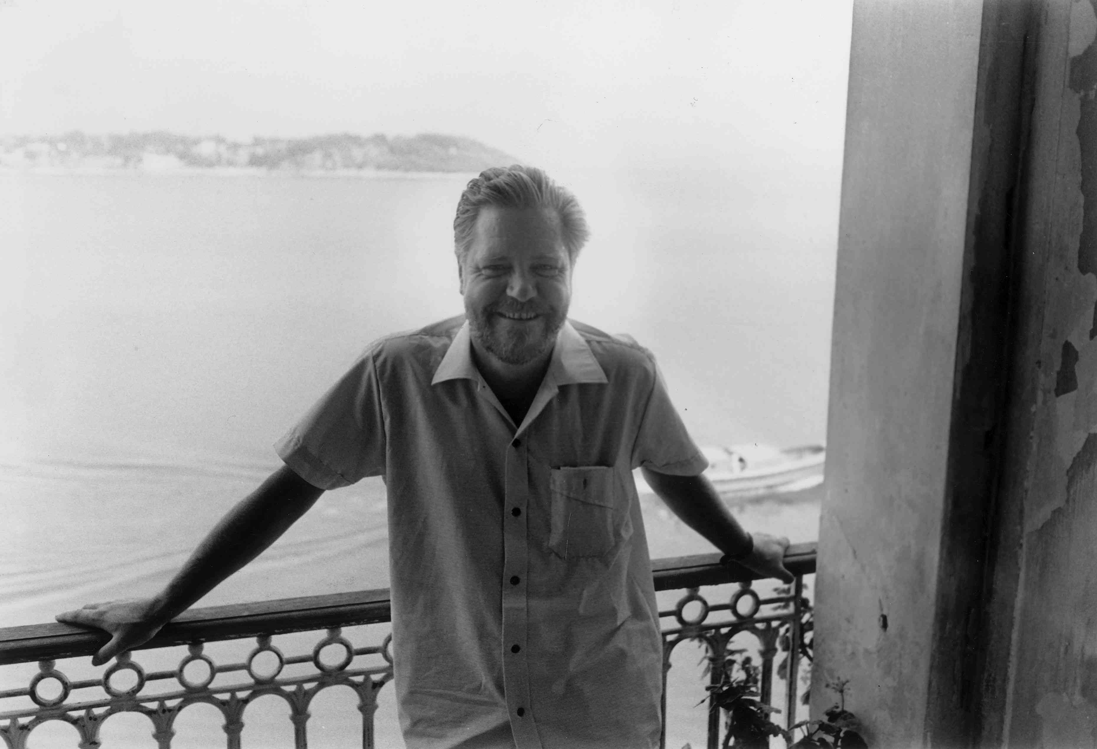 Gerald Durrell posing on balcony in front of water