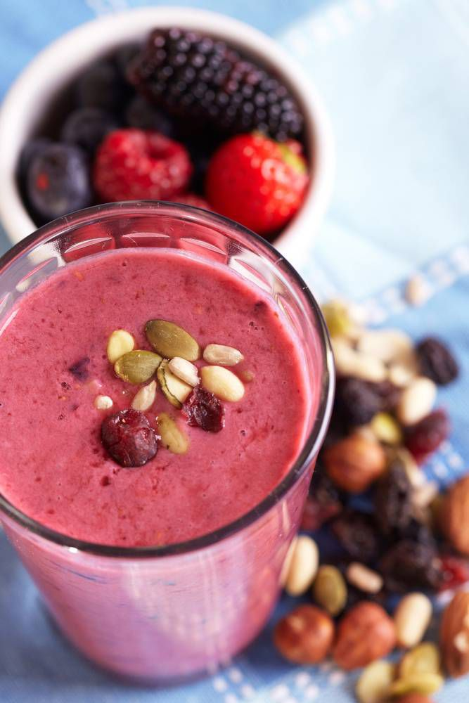 A smoothie surrounded by berries and nuts