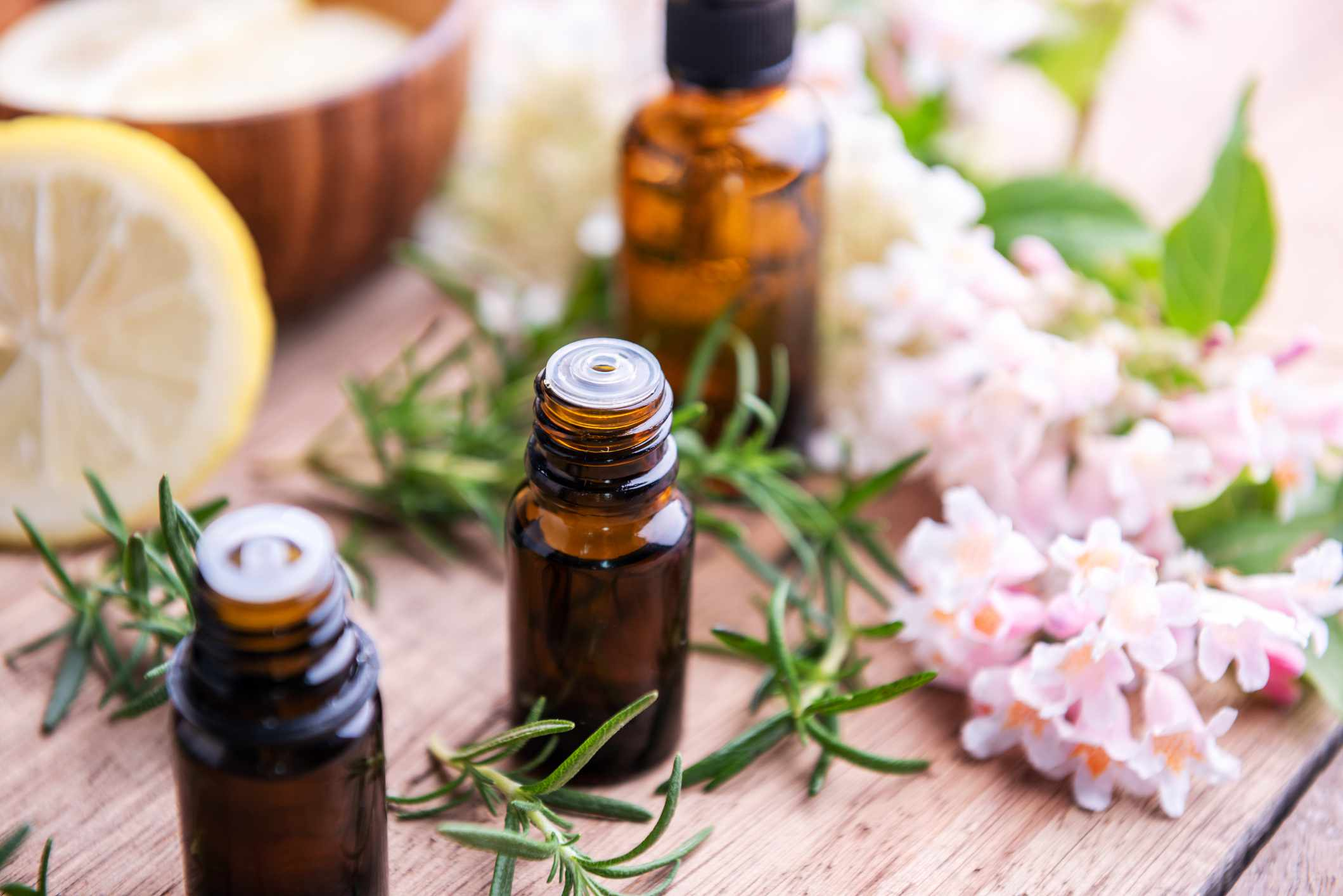 Three bottles of rosemary essential oil sit surrounded by sliced lemon, small pink flowers, rosemary stalks, and a wooden bowl