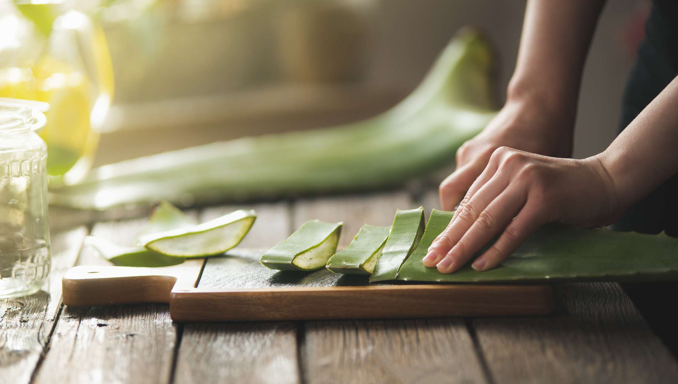 A woman chopping up aloe vera leaves on a wood cutting board.