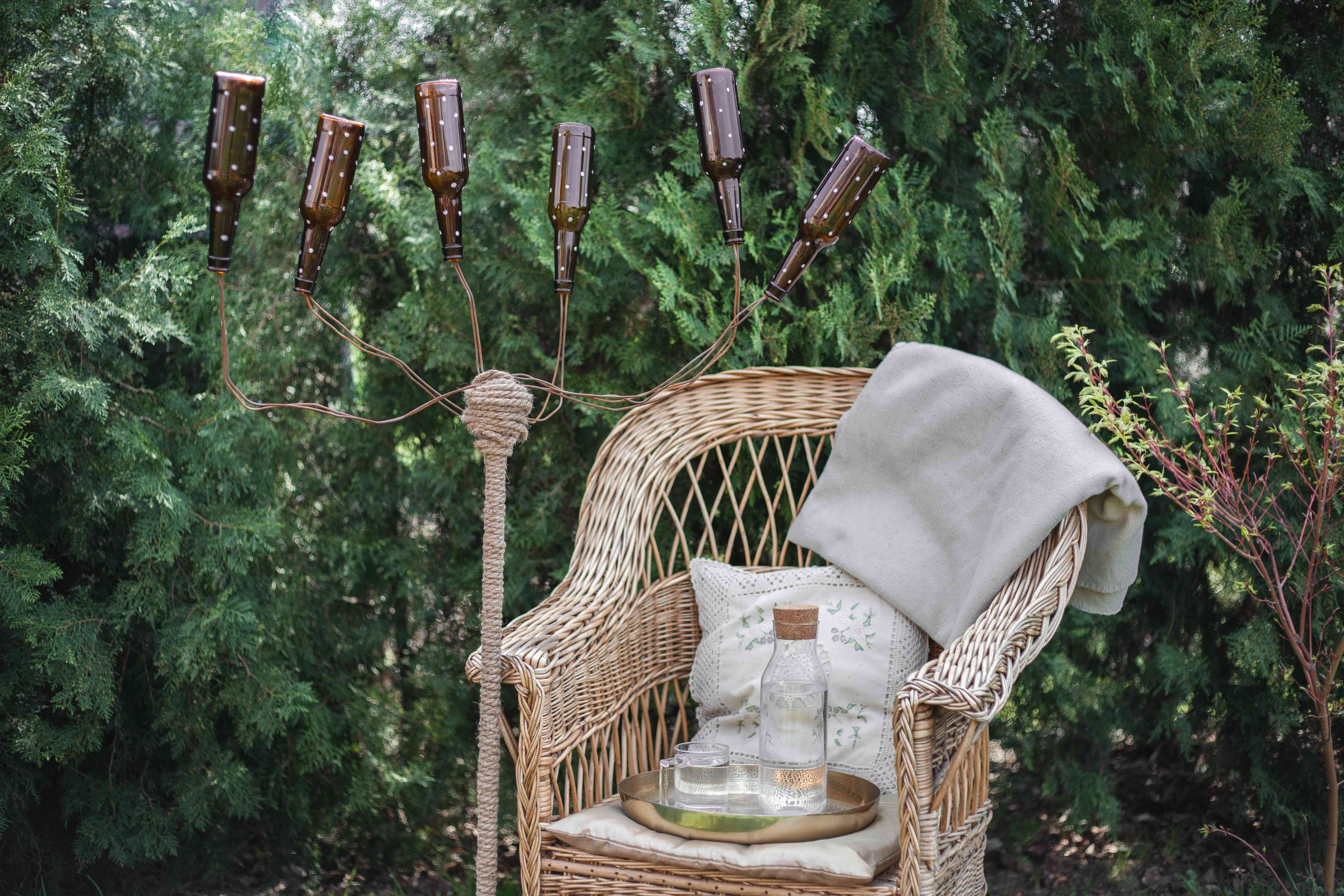 upcycled brown glass bottle tree as outside decor next to wicker chair