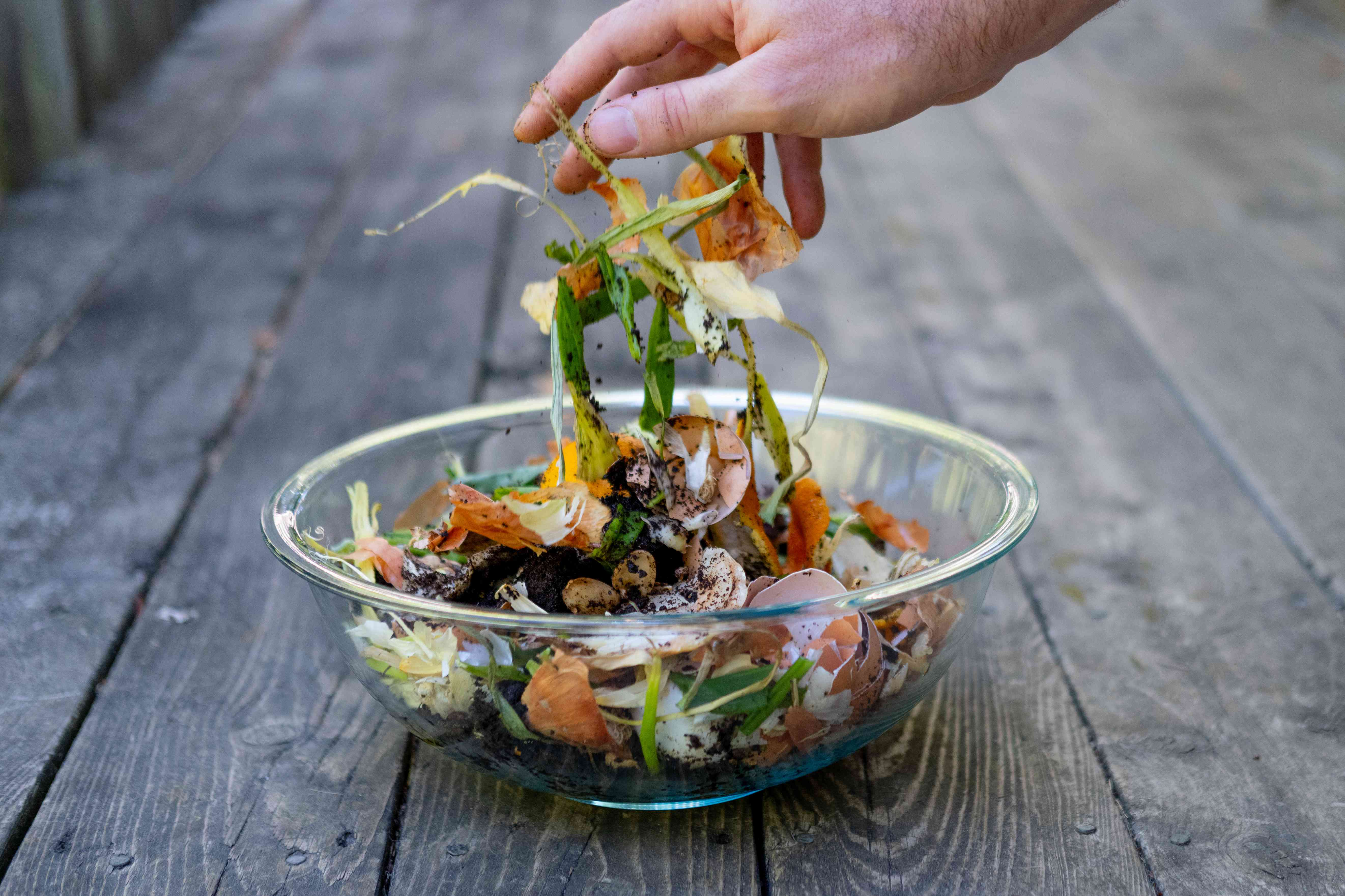 hands drop food scraps into a glass bowl for composting