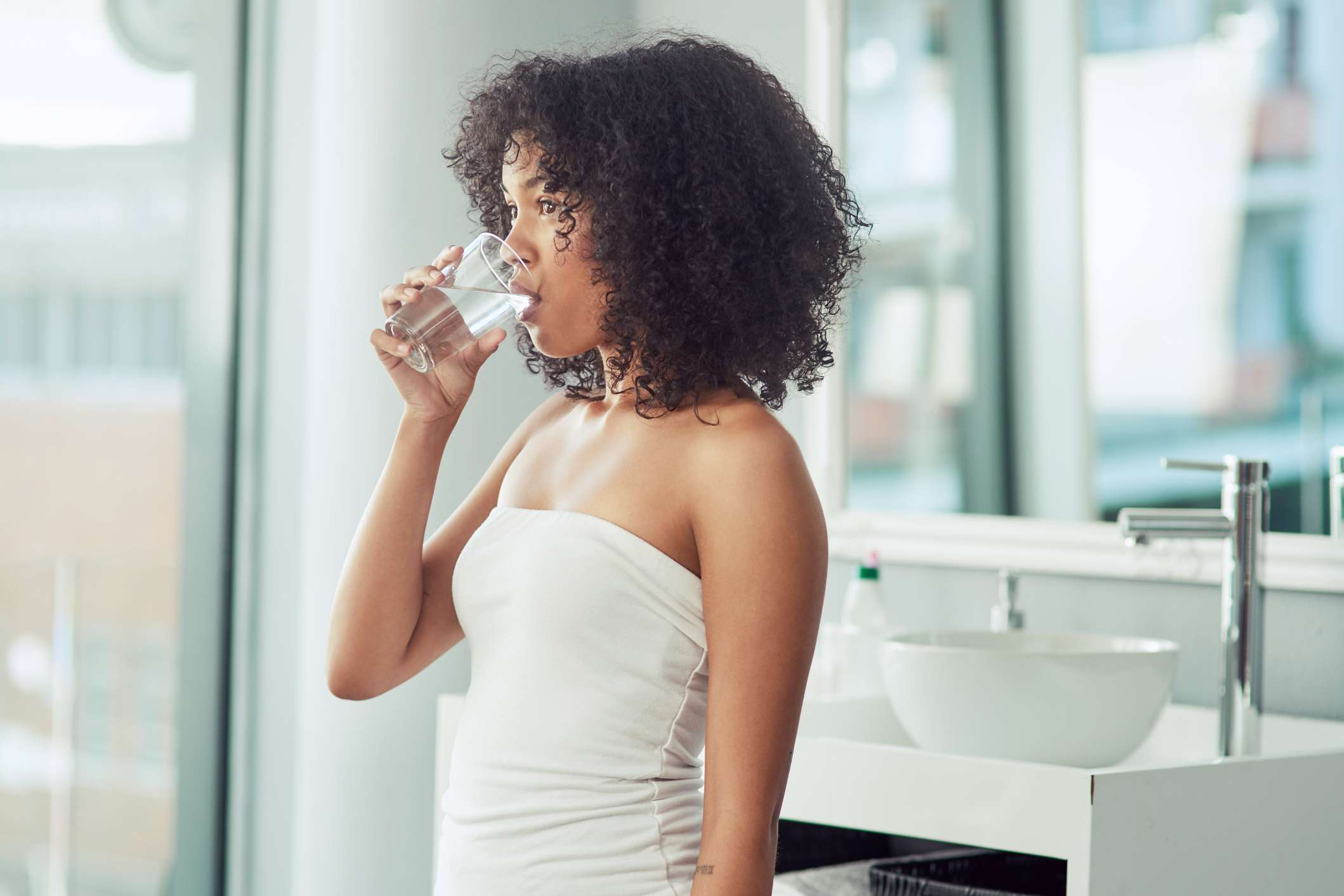 A young black woman drinks water from a glass in a white washroom.