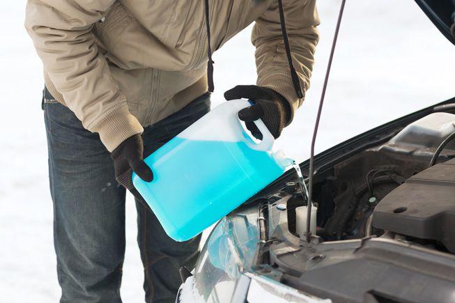 A motorist pours antifreeze into a car during winter