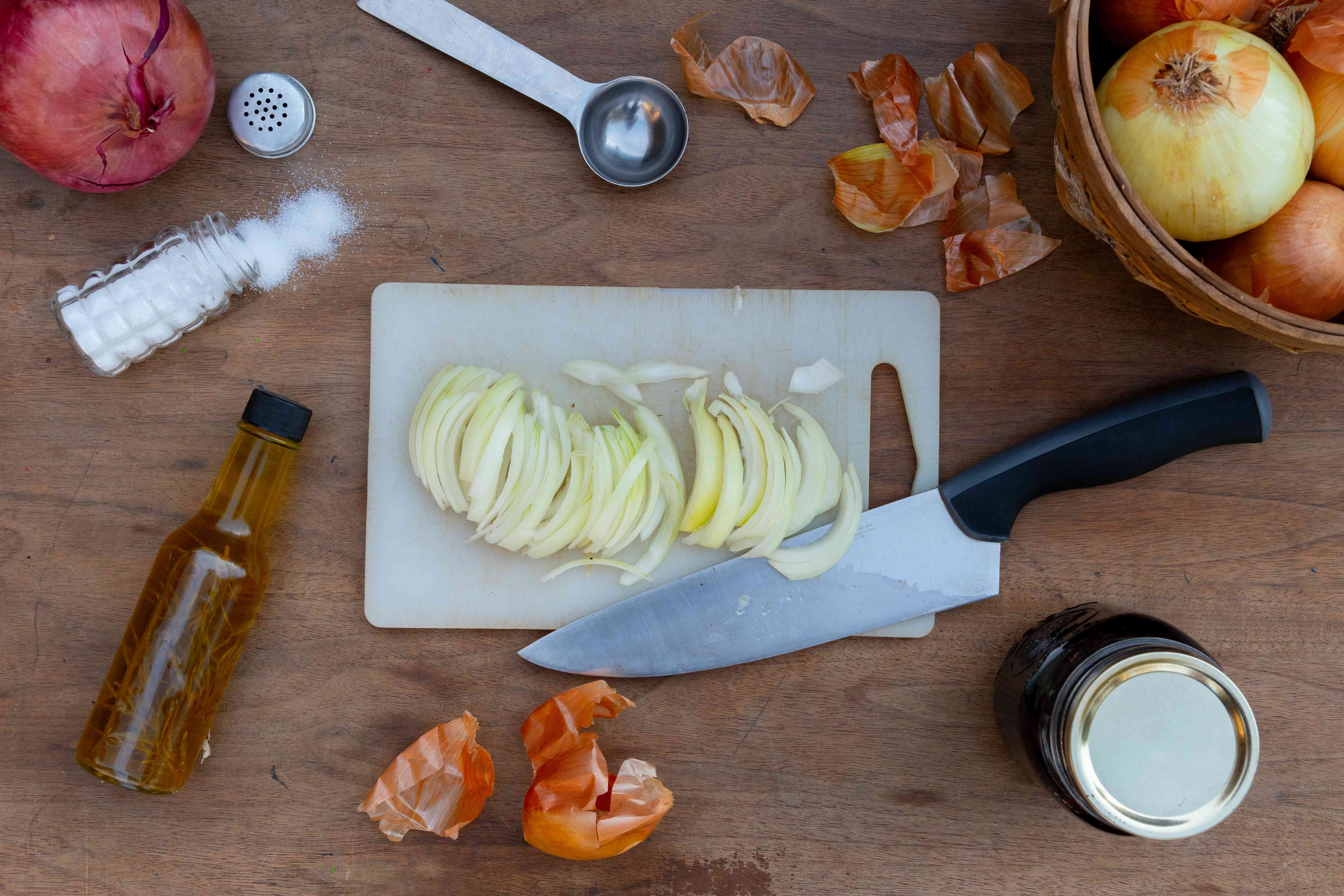cutting up onions on board with other ingredients around