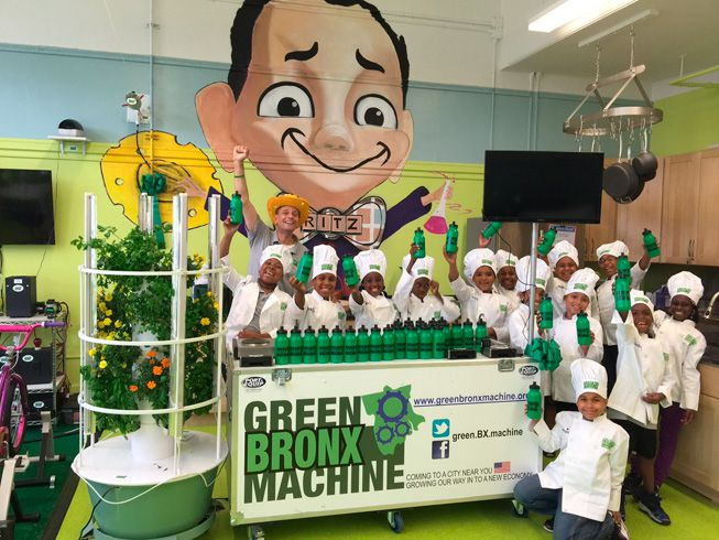 Stephen Ritz poses with students in front of a Green Bronx Machine table in the classroom