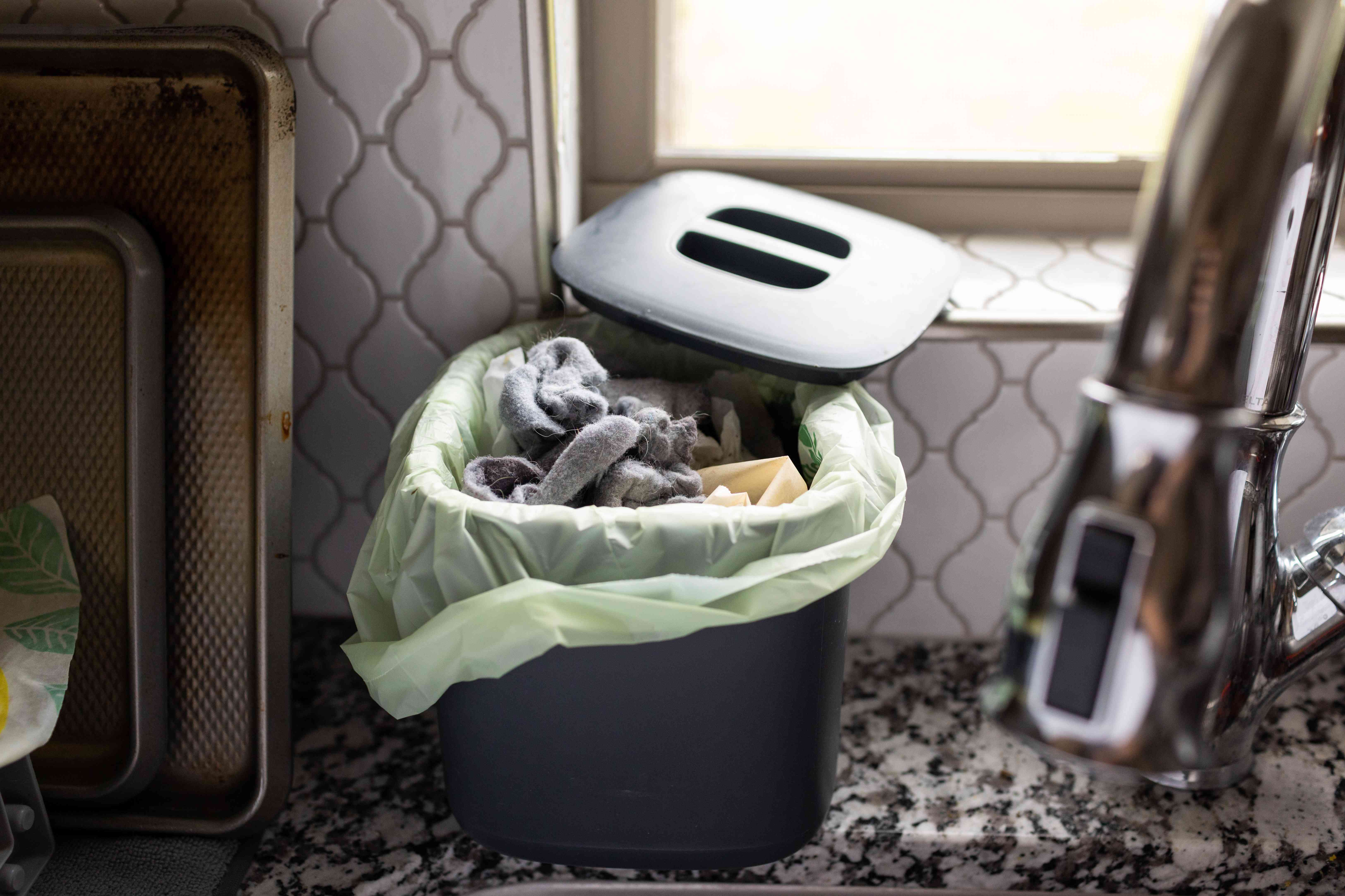 used gray dryer lint is stuffed in kitchen compost bin next to sink
