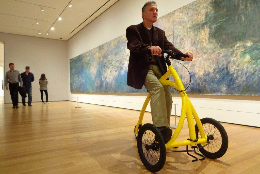 A man riding a walking bike in an art gallery