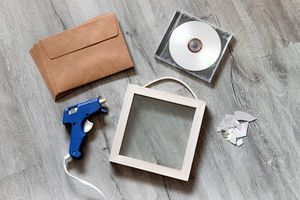 a flat lay shot of cd's and a picture frame and hot glue gun for upcycling