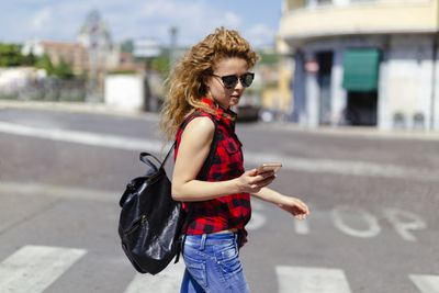 A white woman looking at her phone while she crosses the street.