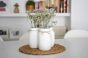 Painted white mason jars with flowers on a table.