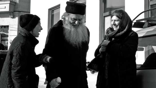 An Orthodox priest and parishioners laugh at while talking together on a sidewalk