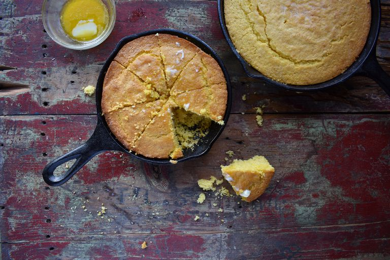 Rustic farm table with buttered corn bread and crumbs
