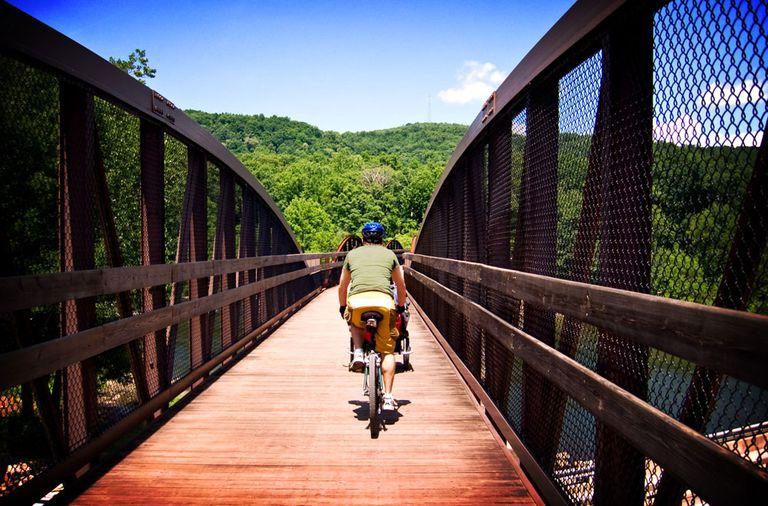 People riding bikes across a wooden bridge
