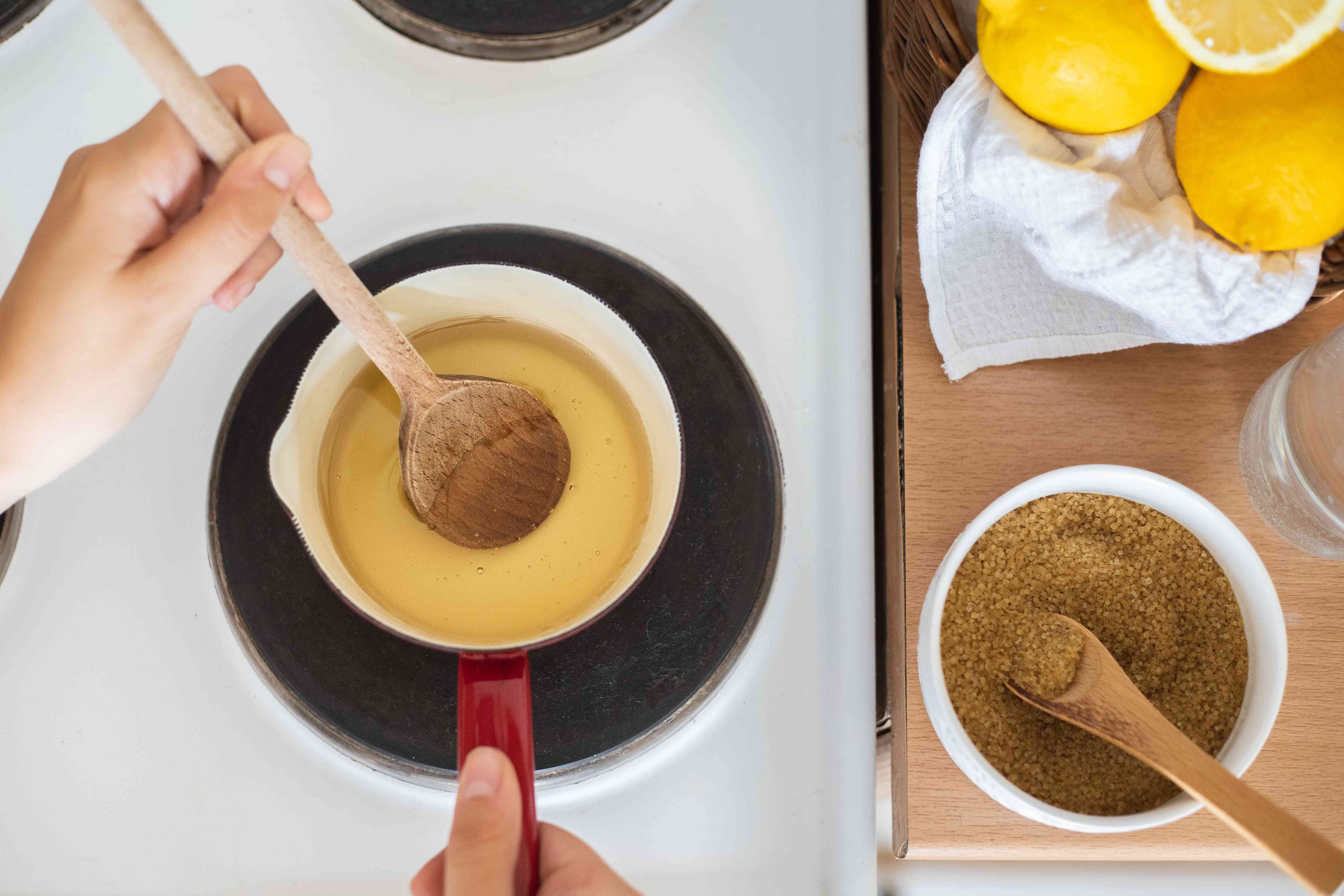 person heats brown sugar on stove with lemon to create homemade sugaring wax