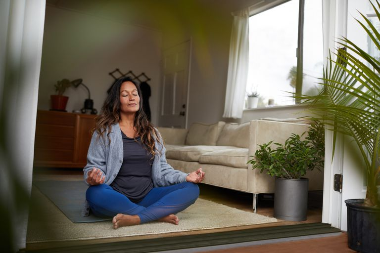 Woman meditating while practicing yoga in her living room