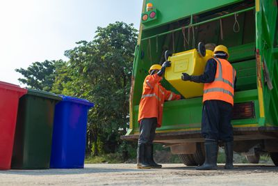 [garbage collector] Asian worker of urban municipal recycling garbage collector truck loading waste and trash bin in Thailand, Trash keeper.