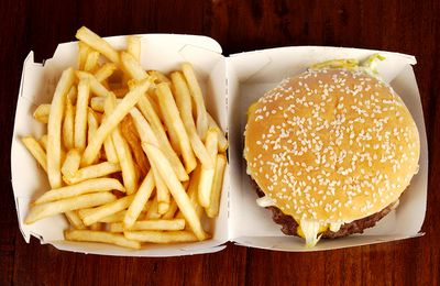 Fast food container with a cheeseburger on one side and fries dumped into the lid
