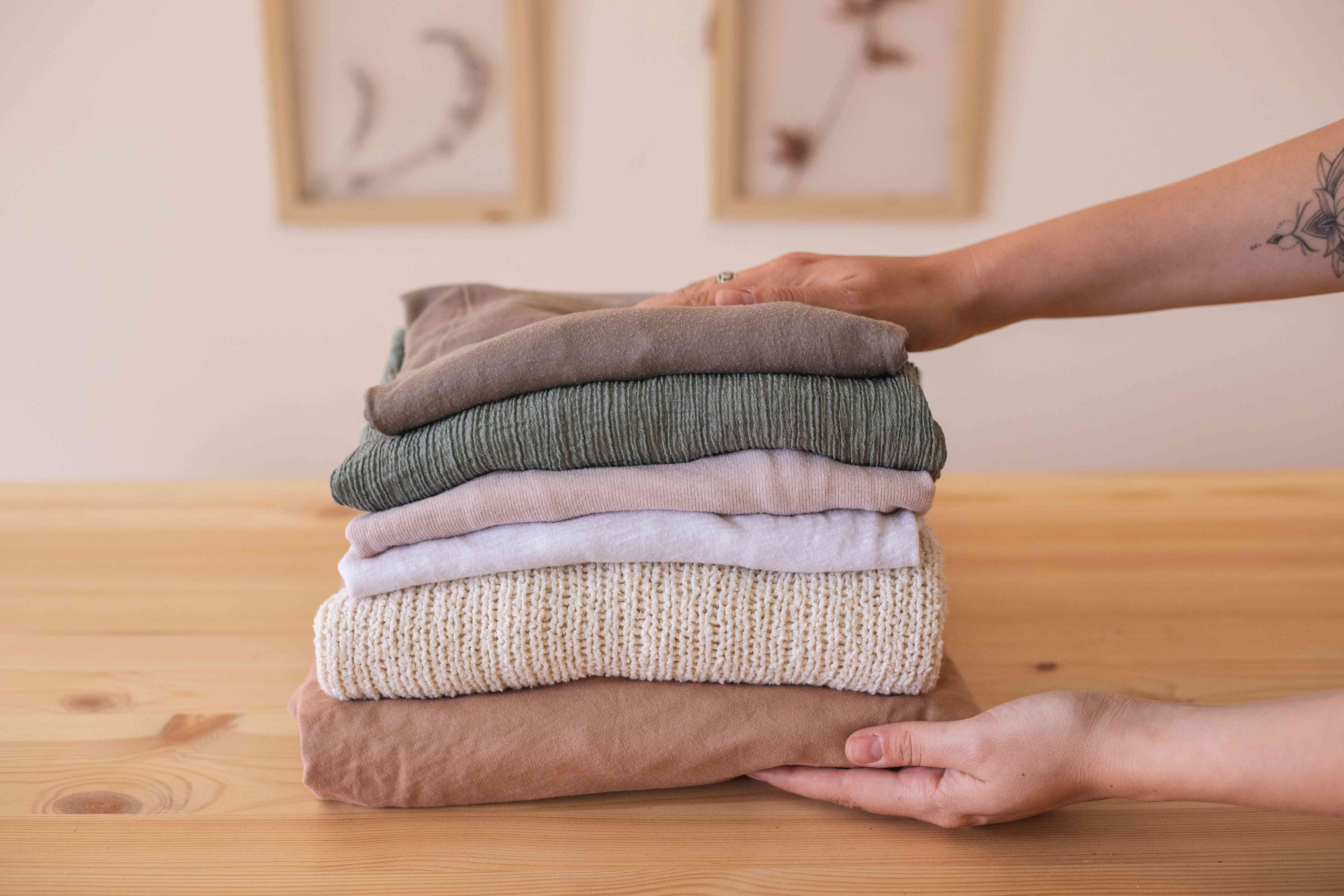 hands reach for neatly folded clothing items on wooden dining table