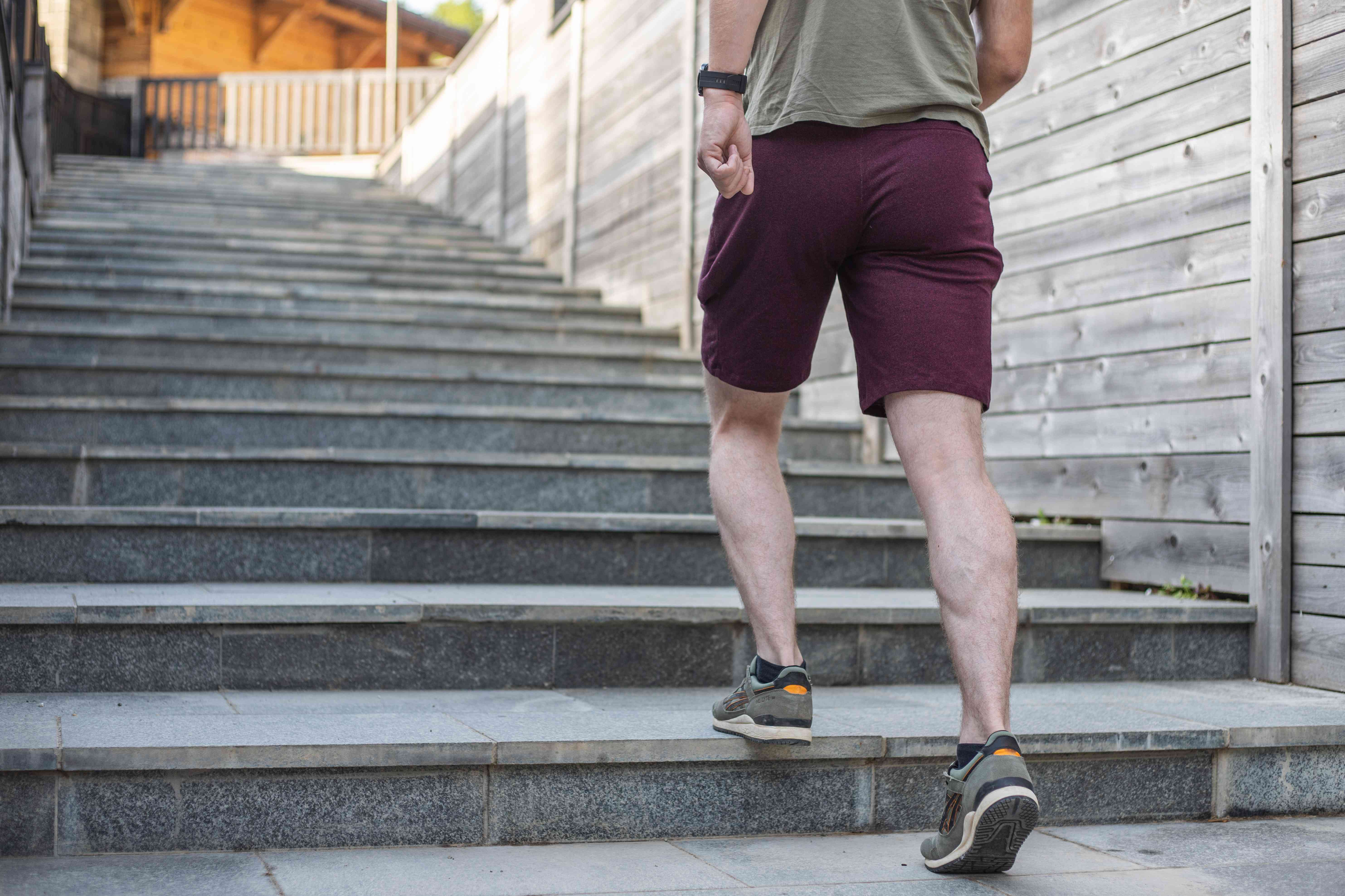 man in maroon shorts and running shoes walks up low-incline stairs outside