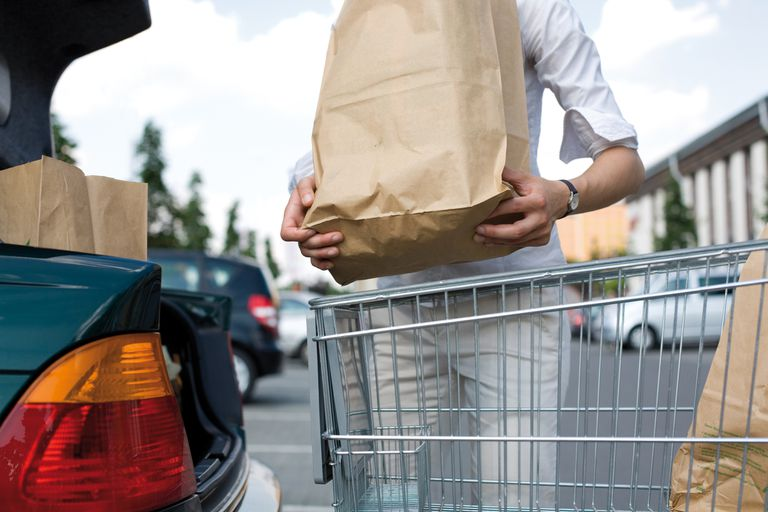 Woman loading paper bags of groceries from a shopping cart into the trunk of her car