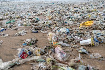 Plastic trash scattered on the beach at Jimbaran beach on January 27, 2021 in Jimbaran, Bali, Indonesia.
