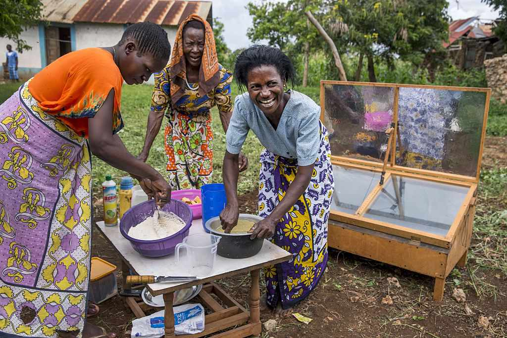 Women in Kenya bake cakes with a solar oven.