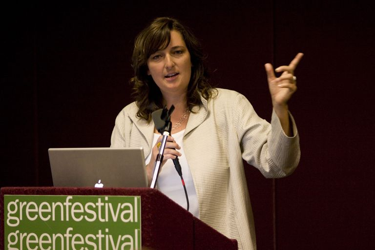 Michelle Kaufmann standing on stage speaking at a green festival event.