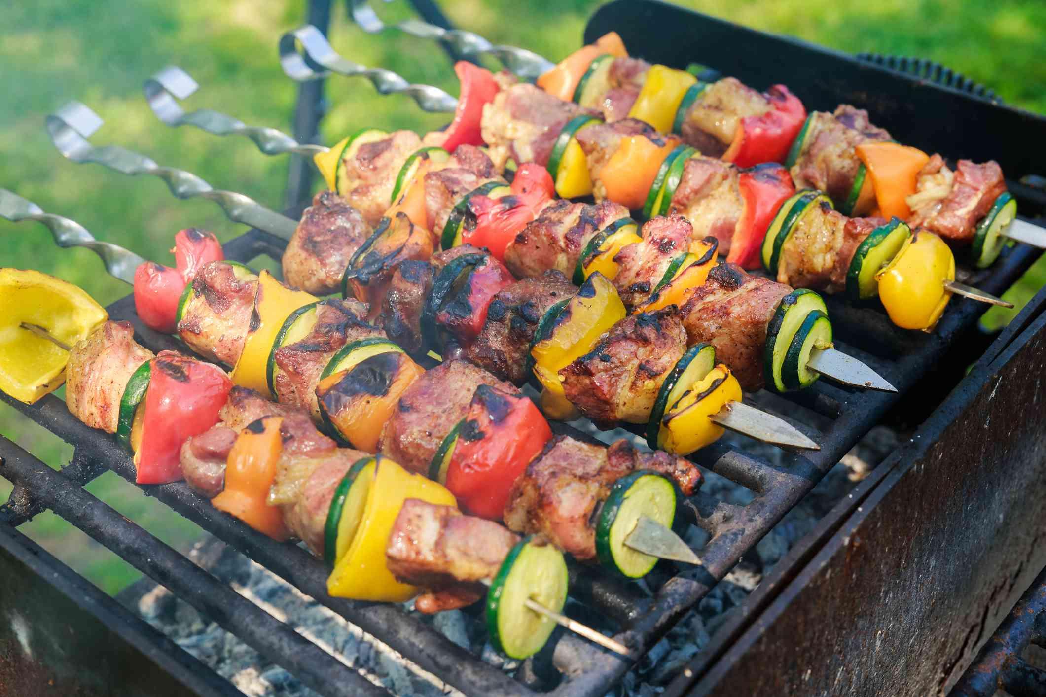 Meat and vegetable kebab skewers on a barbecue.