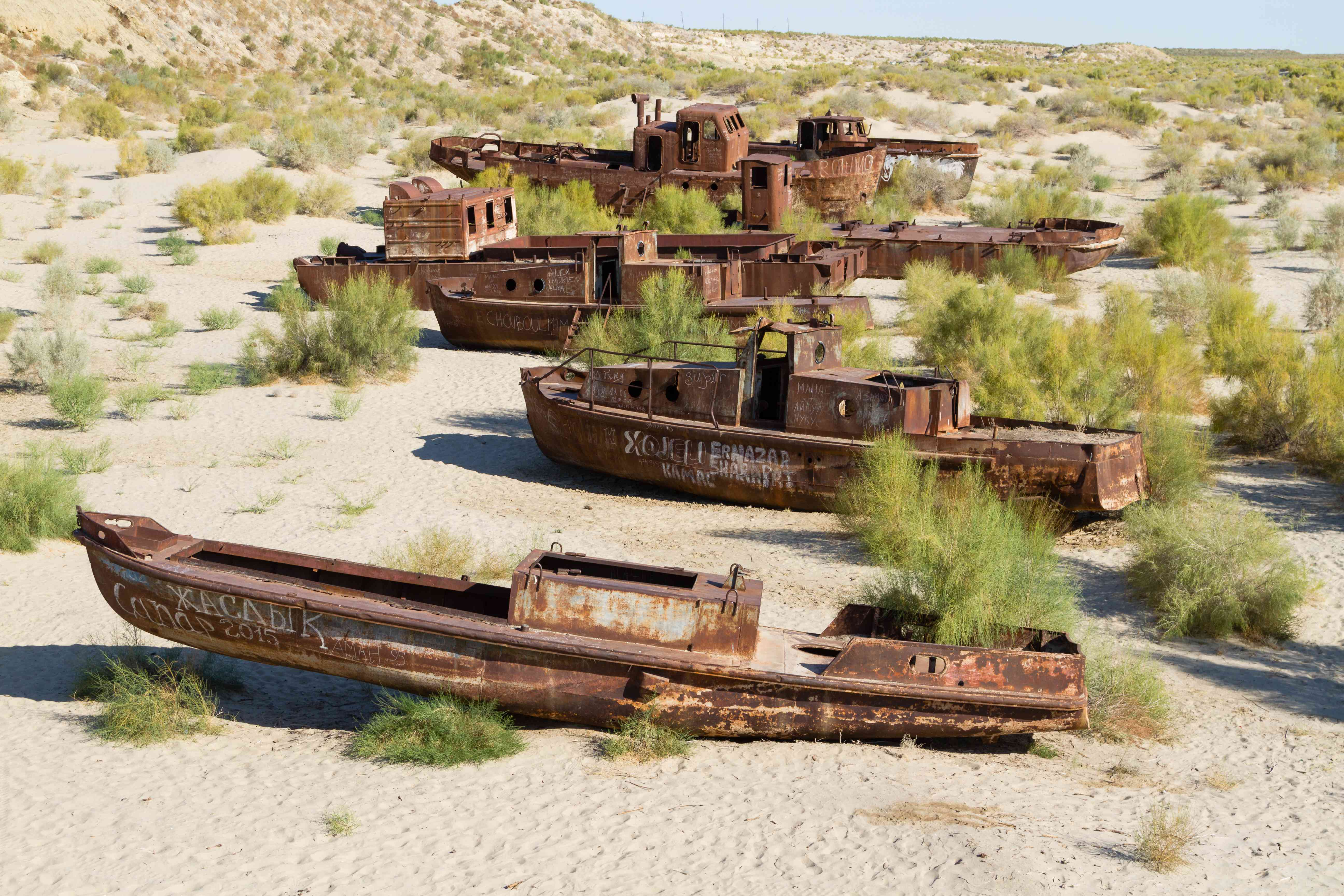 Four rusted boats in the sand of Mo'ynoq