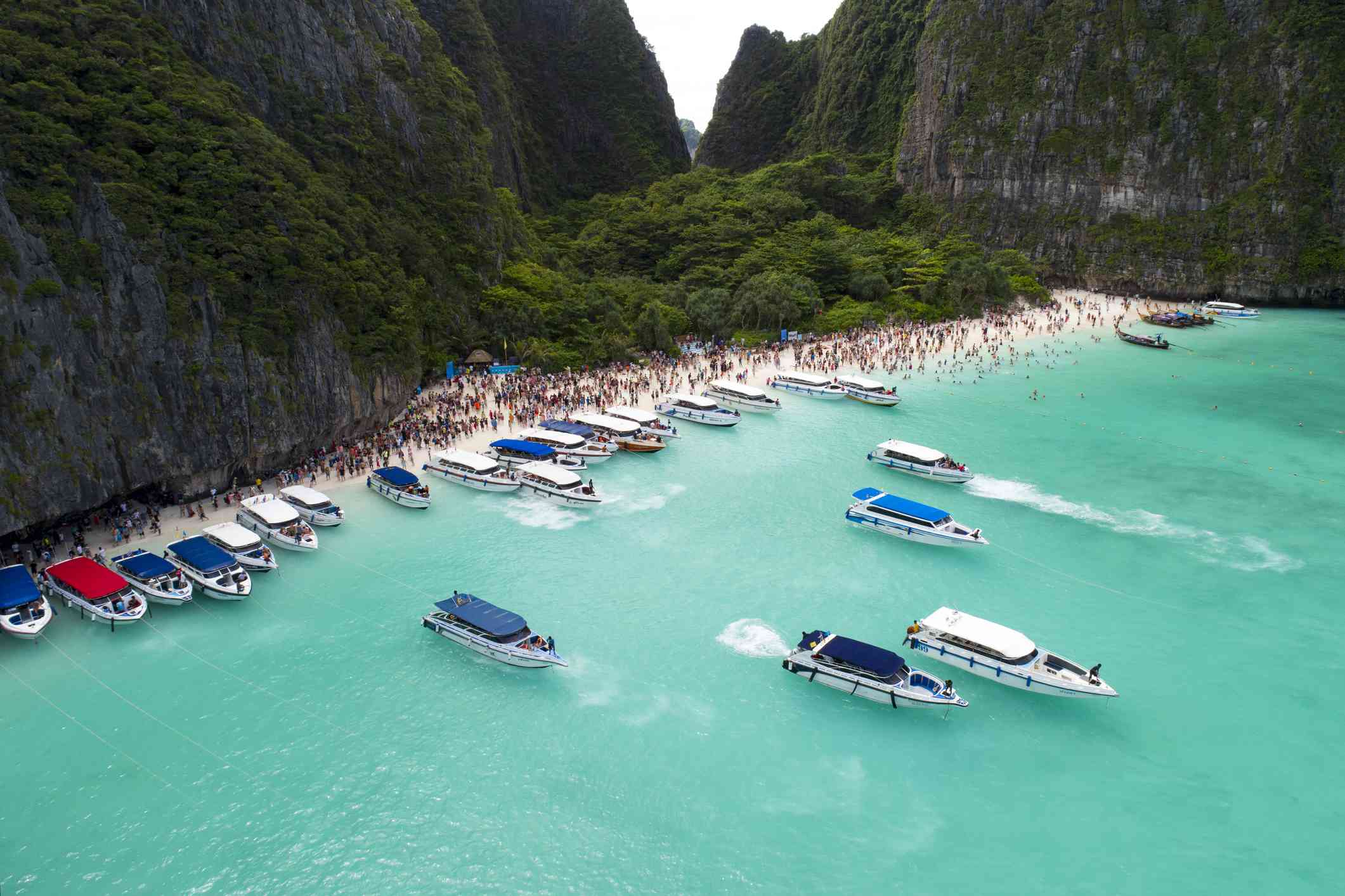 Boats and tourists flock to Maya Bay in Thailand