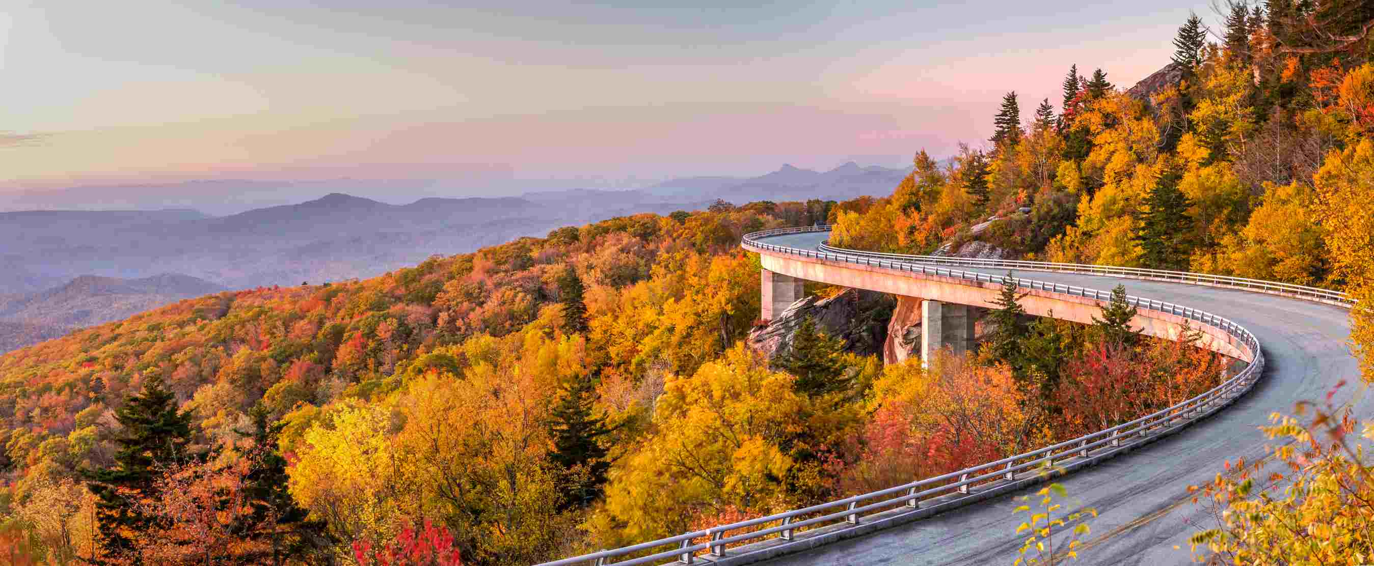 Scenic Blue Ridge Parkway with forest on both sides of the road in peak autumn colors, with mountains in the distance and a pink sunset