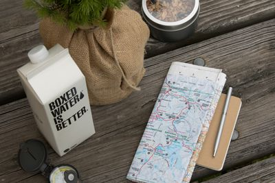 A carton of Boxed Water is Better on a picnic table with a map.