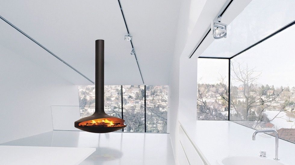 Free floating fireplace in a glass and white room