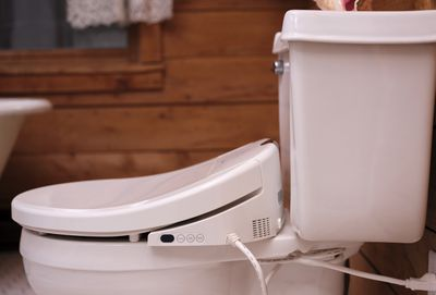 Side view of a white toilet with bidet installed