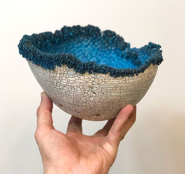 Person holds a ceramic bowl with crystals on the rim