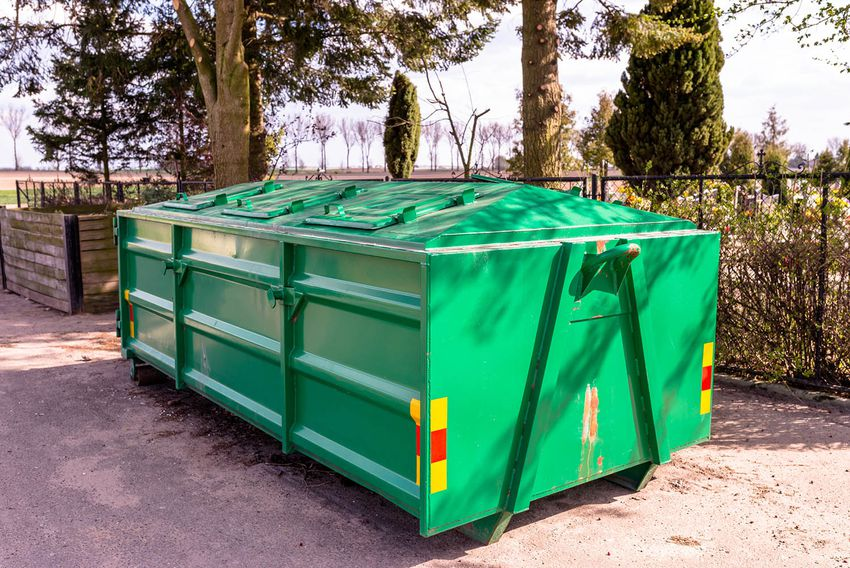 A Large, Metal, Green Garbage Container And Municipal Waste, Standing On A Dirt Road Near The Fence